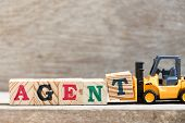 Toy Forklift Hold Letter Block T In Word Agent On Wood Background poster