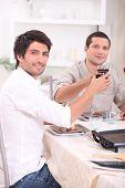 Hombres que tintinea sus vasos en la mesa