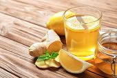Glass With Hot Tea, Lemon And Ginger As Cold Remedies On Wooden Table poster