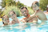 Portrait of happy family at the swimming-pool in summer  poster