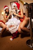 Two sexy girl to have taken Santa Claus like prisoner and   clinking glasses of champagne