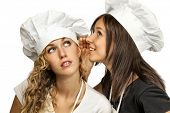 Two young female cookers sharing their secrets, studio shot