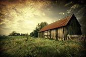 stock photo of old-fashioned  - Old wooden bar with red roof over the dramatic sunset - JPG
