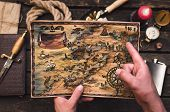 Treasure Map In Treasure Hunter Hands. Pirate Man Learning An Old Map With Red Mark. poster