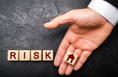 The Realtors Hand Stretches A Cube With A House Pattern To The Word Risk. The Concept Of Risk, Loss poster