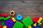 Colored Construction Toys For Children Mockup. Lego Blocks, Minifigures On Dark Wooden Background To poster