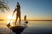 Men, Friends Sail On A Sup Boards In A Rays Of Rising Sun. Stand Up Paddle Boarding - Awesome Active poster