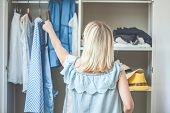 Girl Near A Wardrobe With Clothes Can Not Choose What To Wear. Heavy Choice Concept Has Nothing To W poster