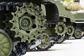 Tank Tracks And Steel Wheels Of Heavy Armored Vehicles With Green Bodywork In Row, Military Industry poster