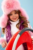 Happy girl in furry hat looking at camera poster