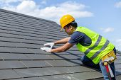 Roof Repair, Worker With White Gloves Replacing Gray Tiles Or Shingles On House With Blue Sky As Bac poster