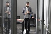Business And Office Lifestyle. Bearded Man Look Out Room Door. Businessman In Modern Office With Gla poster