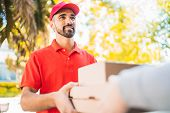 Delivery Man Carrying Packages While Making Home Delivery. poster