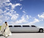 Happy bride and groom about limousine in wedding day
