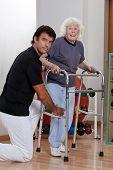 Uma terapeuta ajudando uma mulher sênior para seu walker.