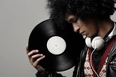 Retro dj portrait in fashion style isolated on grey background in studio. Modern music man with afro
