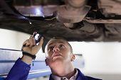 Mechanic holding a flashlight in a garage