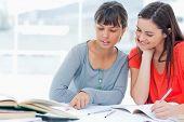 zwei lächelnde Mädchen studieren zusammen und helfen einander, wie sie arbeiten