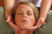 Massaging Face Of Young Woman At Wellness Center
