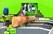 A Large Pine Log Is Automatically Quickly And Accurately Cut At A Modern Sawmill, Receiving The Nece poster