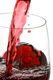 foto of red wine  - Red wine is poured into a glass back lit - JPG