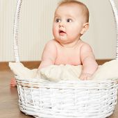 Adorable baby girl in wicker basket