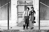 couple waiting for bus, in vintage 1940s clothing