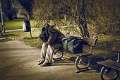 homeless man sitting on a bench in a park