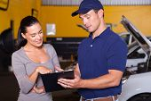 auto mechanic and female customer in garage