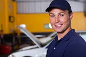 portrait of trustworthy auto mechanic inside workshop
