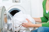 Young woman or housekeeper has a laundry day at home, she takes the laundry or whites out of your washing machine or the dryer