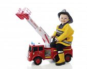 stock photo of fireman  - An adorable toddler happily playing fireman on his toy fire truck - JPG