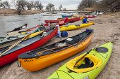 SOUTH PLATTE RIVER, EVANS, COLORADO - APRIL 6: Kayaks and canoes on a river shore below diversion dam during Annual All Club Paddle on April 6, 2013, a popular season opening paddling trip.