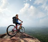 Young woman athlete standing on top of a mountain with red bicycle and enjoying valley view