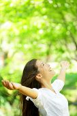 picture of arms race  - Happy woman rejoice looking up happy enjoying spring or summer forest park smiling with arms outstretched - JPG