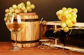 Wooden case with wine bottle, barrel, wineglass and grape on wooden table on brown background