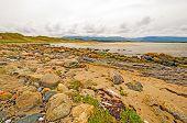 Sand und Felsen wo Meer und Fluss-treffen