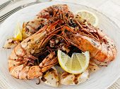 Jumbo prawns and grilled squids with black rice and lemon, close-up