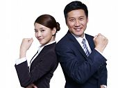 stock photo of fist  - asian businessman and businesswoman standing back to back making a fist - JPG
