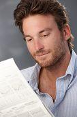 Retrato de bem parecido sorrindo jornal de leitura do homem.