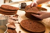stock photo of tort  - Chef cutting chocolate cake layers and stacking them - JPG