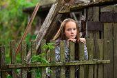Teengirl standing near vintage rural fence.