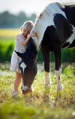 stock photo of paint horse  - Child stands with a horse in the field - JPG