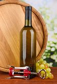 Composition of corkscrew and bottle of wine, grape, wooden barrel  on wooden table on bright backgro