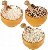Assortment of rice in wooden dish and scoop  isolated on white background