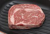 A gourmet Australian wagyu ribeye steak in a grill-pan