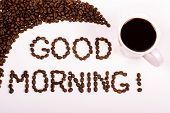 good morning written in the coffee beans with a filled coffee cup