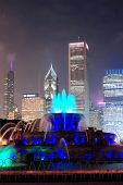 Chicago skyline with skyscrapers and Buckingham fountain in Grant Park at night lit by colorful ligh