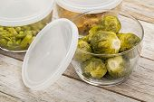 dinner meal or leftovers (chicken, brussels sprouts, asparagus, green pea) stored in glass container