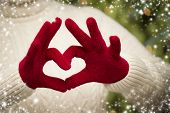 Woman in Sweater with Seasonal Red Mittens Holding Out a Heart Sign with Her Hands with Snow Flakes Border.